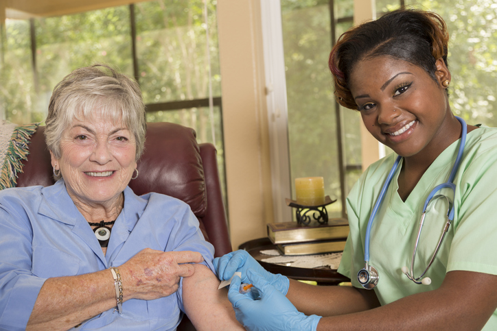 Home healthcare nurse giving injection to senior adult woman