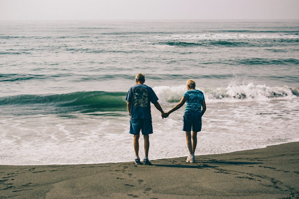 couple holding hands near the ocean