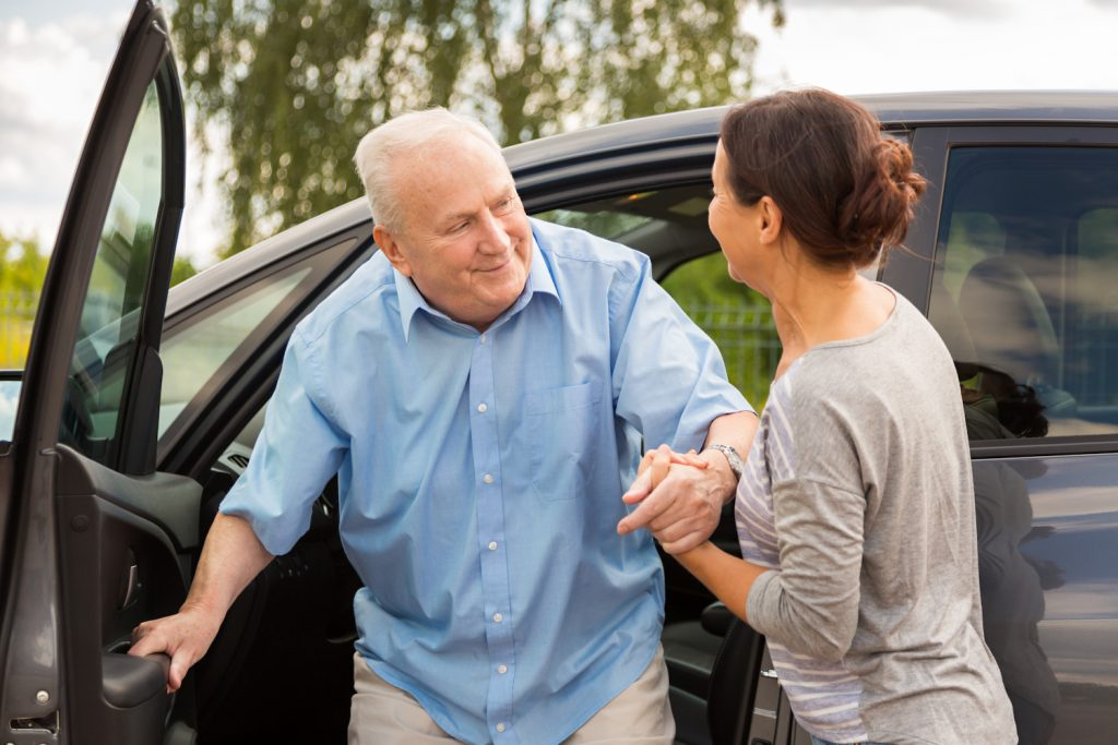 Woman helping senior out of the car